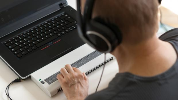 A person using a laptop computer wearing headphones and touching a braille output device.