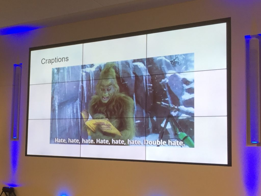 projected slide with title of craptions and the grinch with caption saying hate hate hate double hate